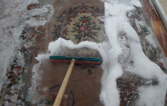 Cleaning a Chinese wool rug in our rug washing pit showing the shampoo being brushed through the fibres